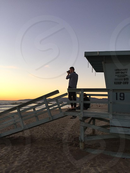 woman in grey dress shirt taking a picture on beach while standing on life guard shed photo