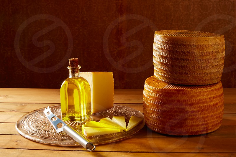 Manchego cheese from Spain in wooden table with andalusian olive oil photo