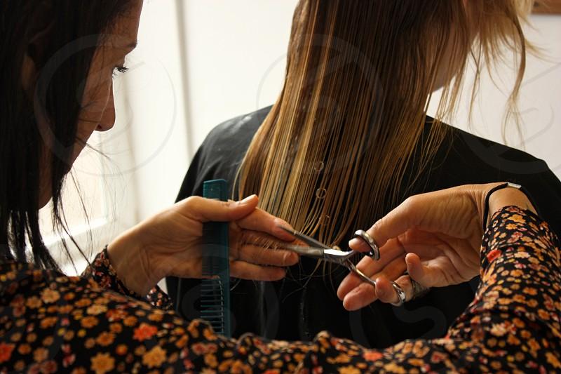 A hairdresser at work cutting a woman's hair photo