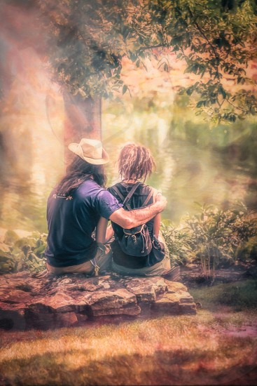 man and woman sitting and looking onto river painting photo