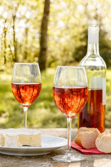 Two glasses of rosé wine next to a bottle of rosé wine of course with cheese and bread laid on a table outdoor. Trees can be seen out-of-focus in the background photo