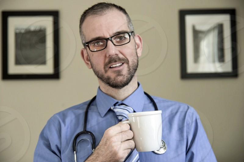 Doctor on web call holding coffee photo