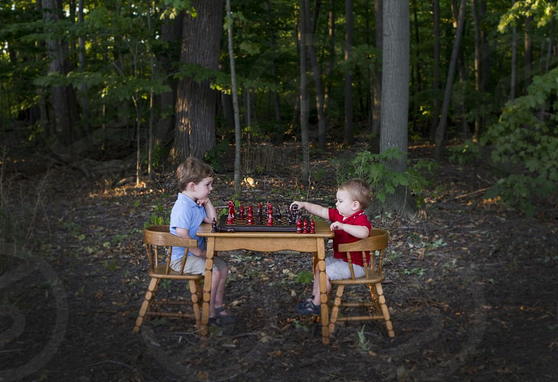 Boys playing chess in the forest.  Summer fun! photo