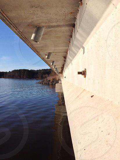 photo of under beige concrete bridge near trees under blue sky during daytime photo