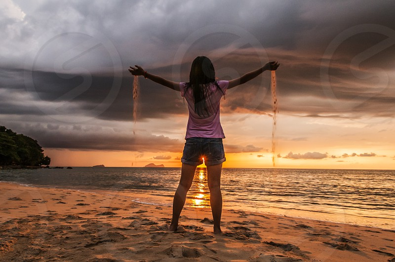 sunset beach teen girl sand sifting hands outstretched asian people one person teenage female alone summer vacation holiday freedom tranquil serene harmony concepts evening dusk horizontal photo