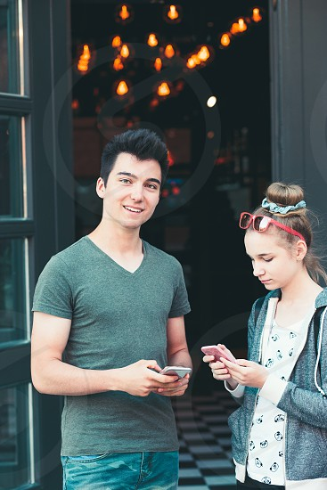Couple of friends teenage girl and boy  using smartphones talking together standing on street in center of town spending time together photo