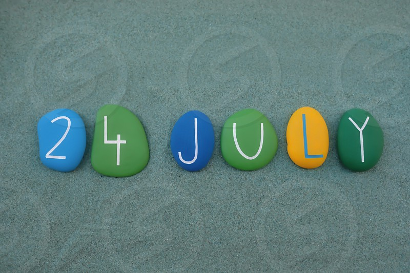 24 July calendar date composed with multi colored stones over green sand photo