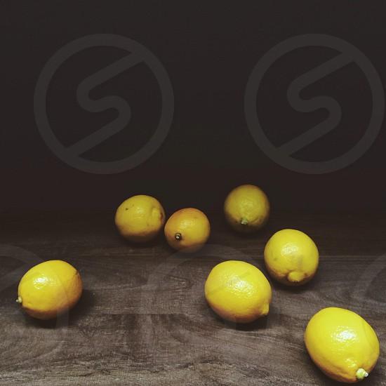 yellow lemons on a dark wood table photo