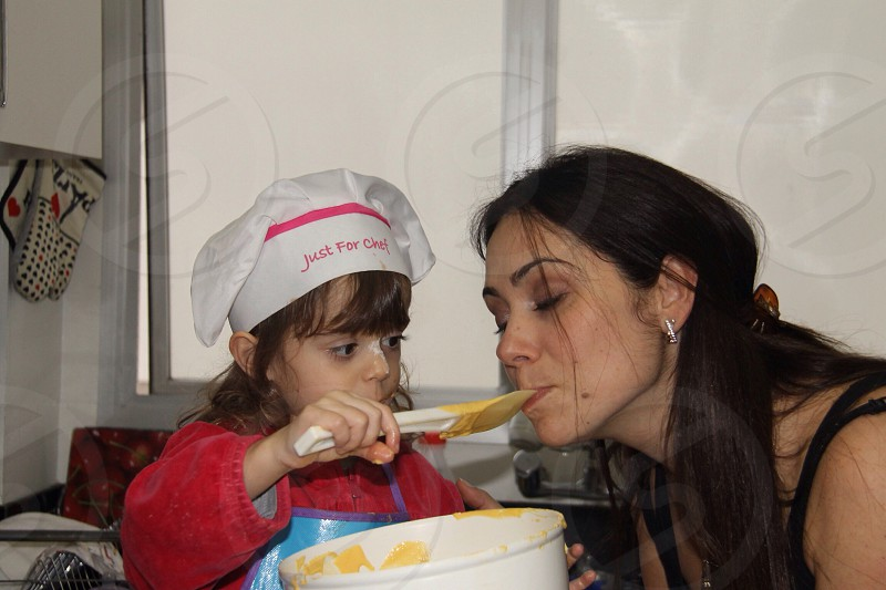 girl baking using a white spatula and white mixing bowl photo