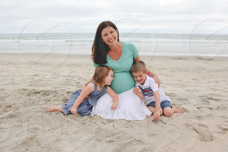 woman in green t shirt in the middle of 2 toddler while sitting on sand during daytime photo