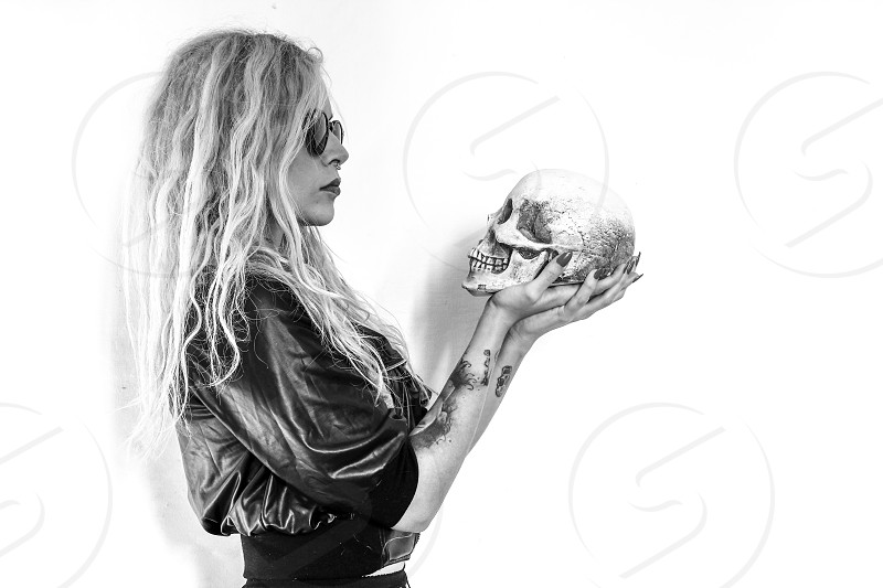 A girl looks death in the face holds in his hand a skull photo