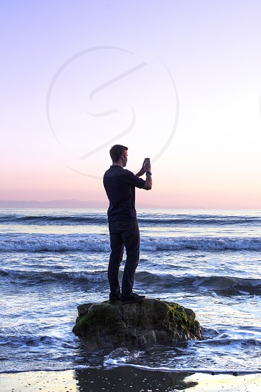 Man holding iPhone to take picture at the beach during sunset.   photo