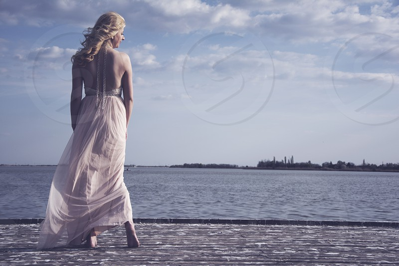 Beautiful young blond woman in evening gown posing on deck at lake. photo