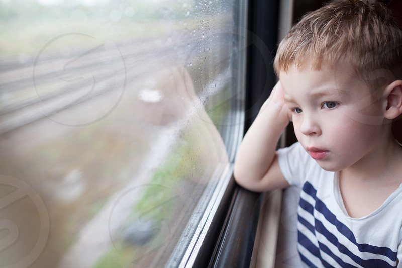 Curious boy looking out the window of a speeding train photo