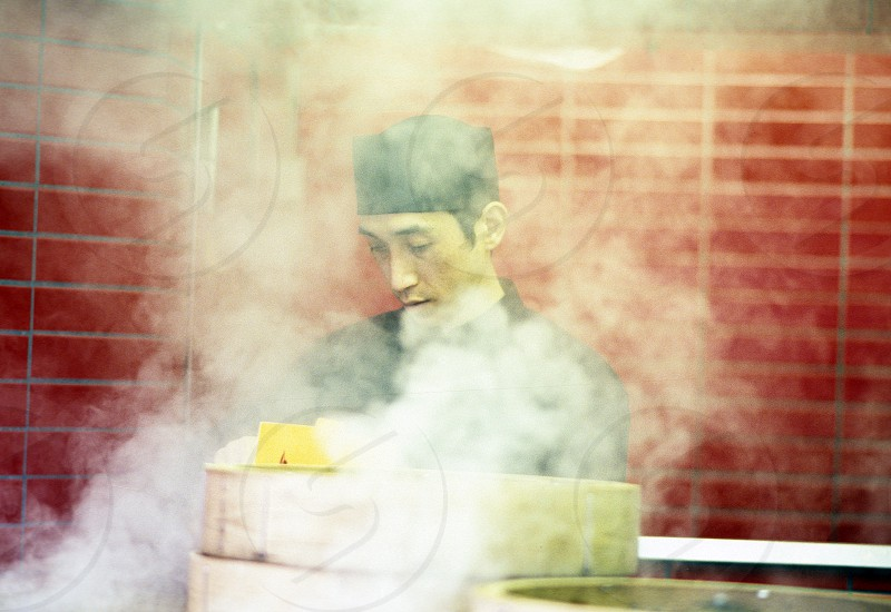 Japanese chef cooking in a restaurant with smoke covering him from his pots and pans photo