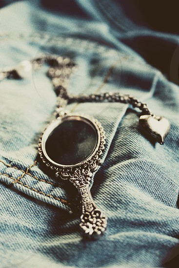 black and grey metal pendant on jeans photo