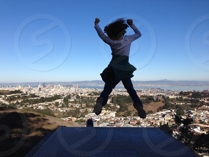city view from the top through a girl jumping photo