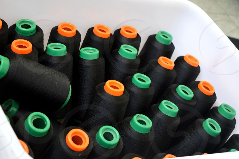 Black thin wrapped sewing thread in the basket. photo