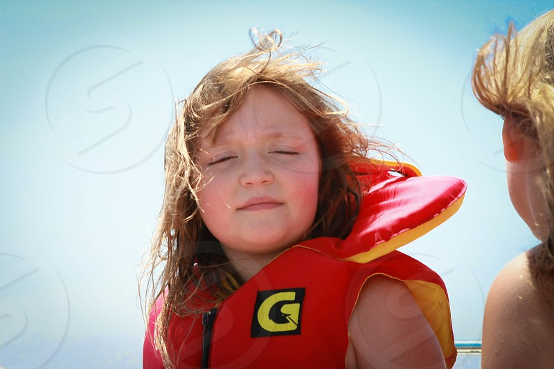 girl in red inflated vest with G print photo