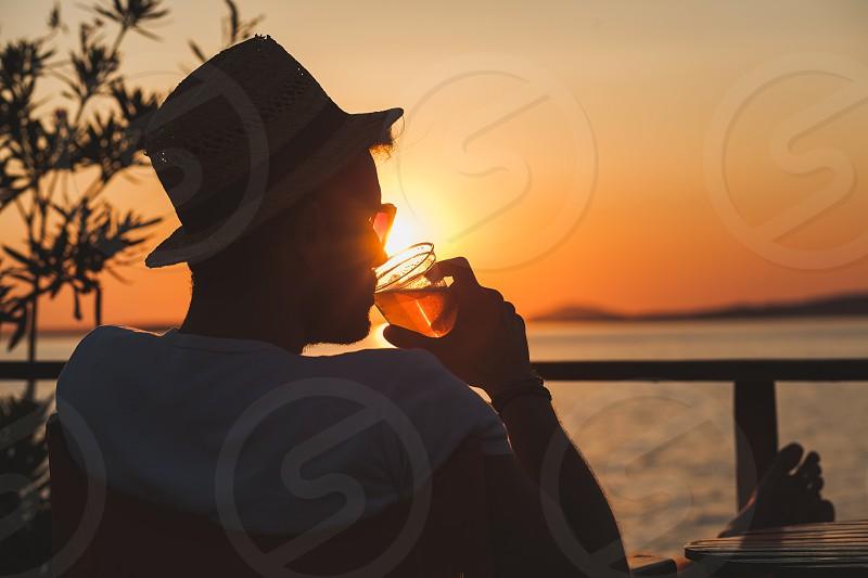 Young man enjoying sunset at a beach bar photo