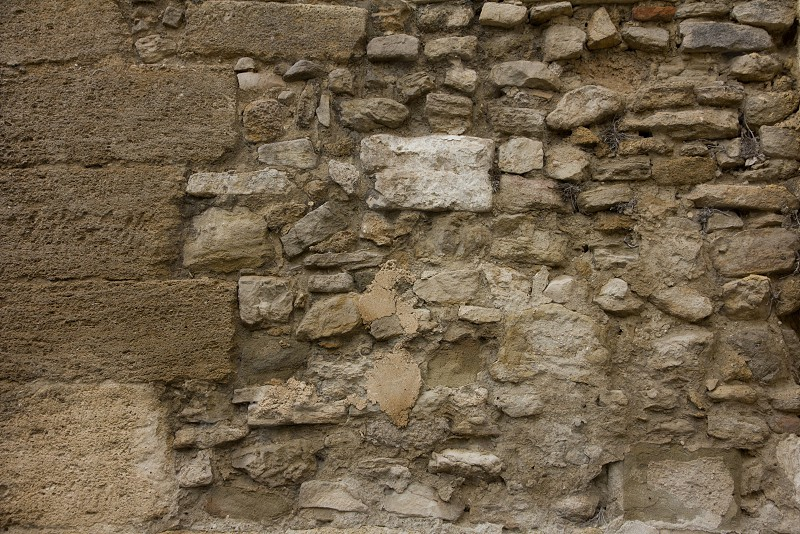Background image old stone wall filled with all sizes of rock photo