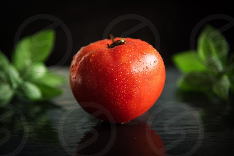 Tomato with basil on a dark background with water drops. photo