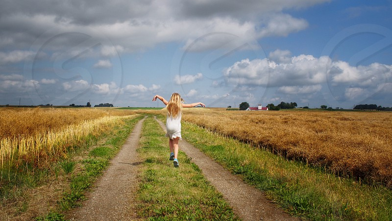 Rear view young girl dancing happy playing road field photo