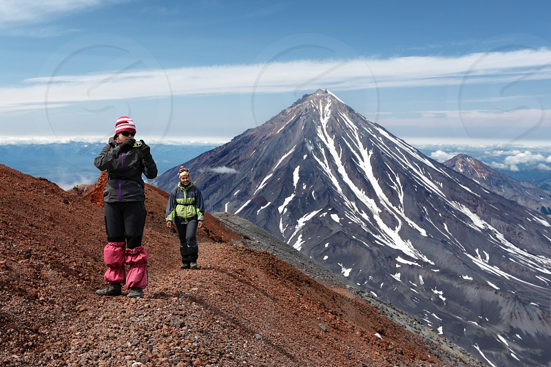 AVACHA VOLCANO KAMCHATKA PENINSULA RUSSIA - AUG 7 2014: Two young women tourists are walking along a mountain hiking trail on edge of crater of active volcano and photographing volcanic landscape. photo