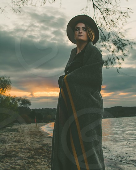female in black hat covered in green and brown blanket standing in gray sand beach under gray cloudy sky photo