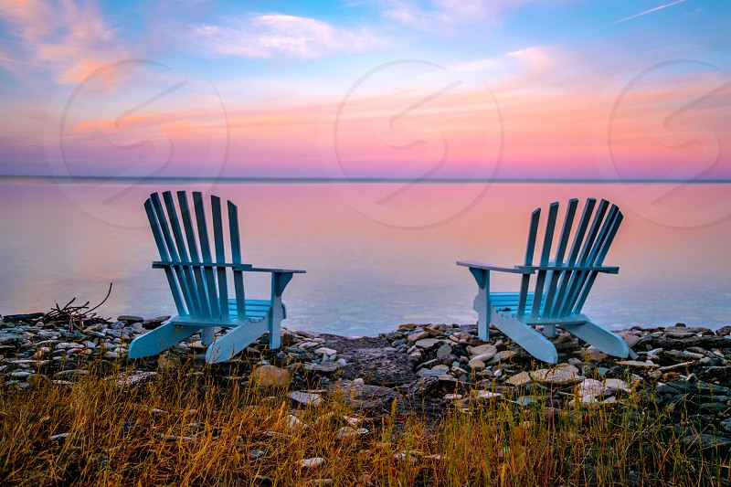 Two chairs sit empty at a colourful sunrise. photo