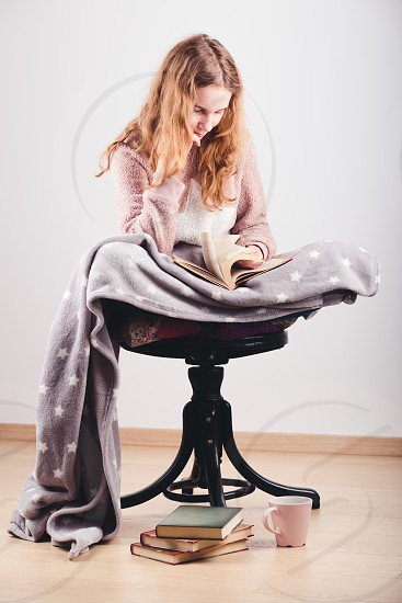 Girl enjoying the reading a book and drinking coffee at home. Young woman sitting on a chair wrapped in blanket holding book relaxing at home. Portrait orientation. Front view photo