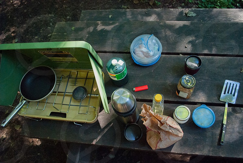 Coleman stove food and Thermos on picnic table in the woods  photo
