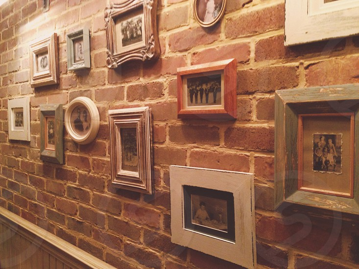 Beautiful arrangement of antique/urban looking frames on a brick wall. photo
