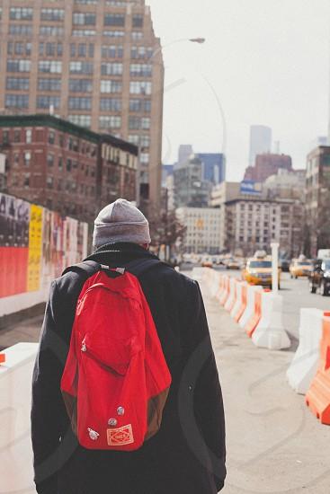 man in black jacket and gray beanie walking on side walks photo