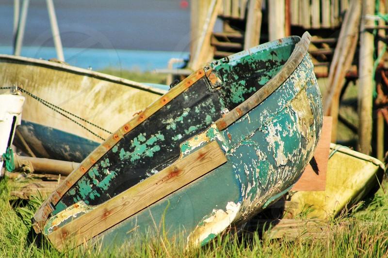 Boatyardoldboatholeswoodenpeelingpaintrustynailsgrassondrylanddock photo