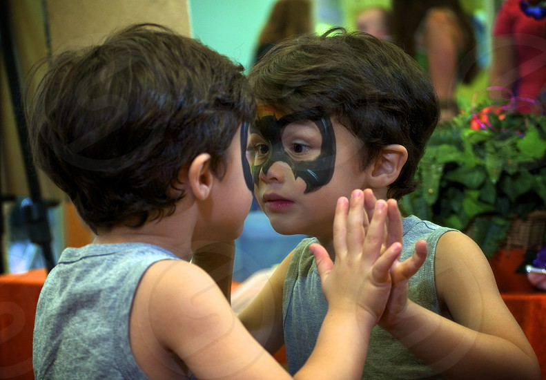 Young boy amazed at his transformation as he stairs at the reflection of his face-paint in a mirror.  photo