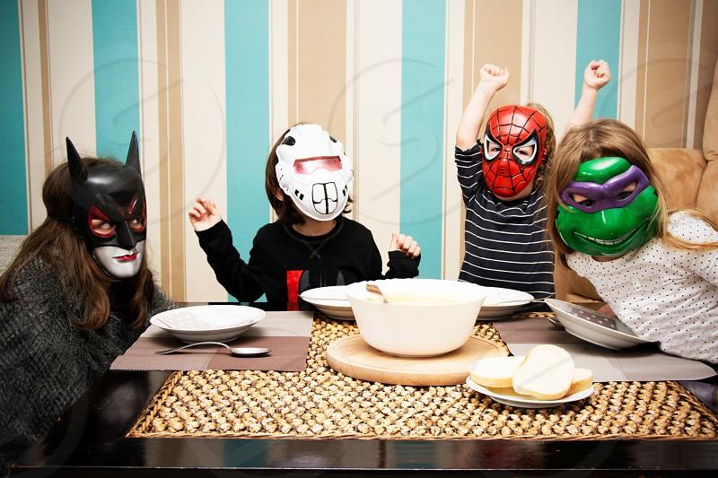 Children in super hero masks dinner photo