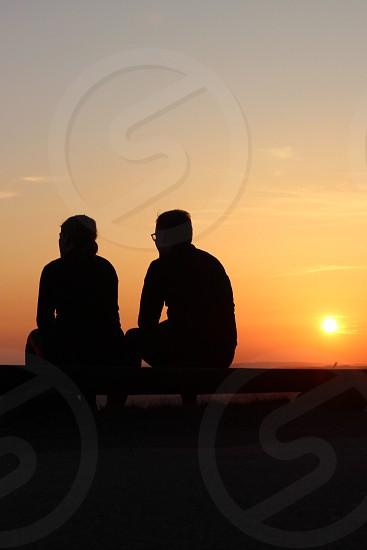 outline of two seated figures by sunset photo