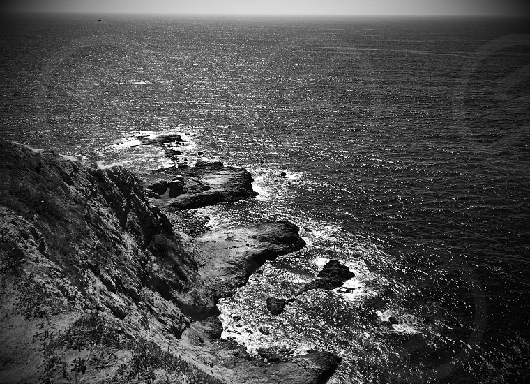 grayscale and bird's eye view photography of cliff near body of water photo