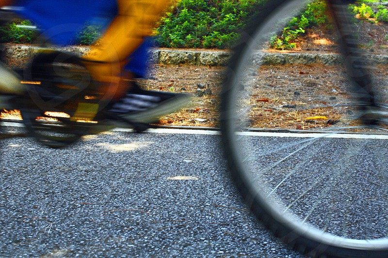 Blurred detail of a wheel and  feet pedaling a bicycle. photo