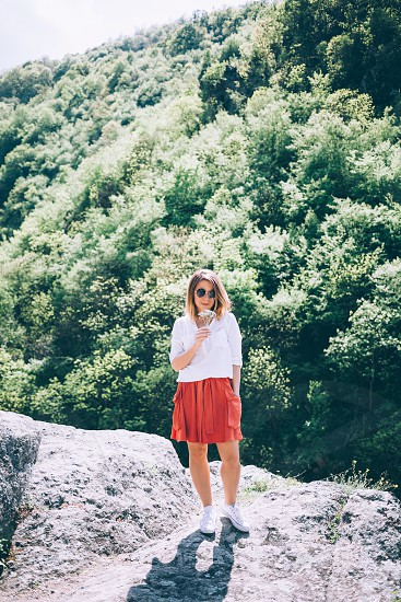 Young woman on the rock in nature with flowers in her hands photo