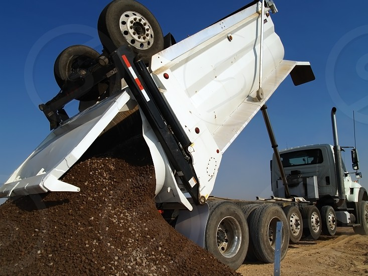 A large heavy duty dump truck depositing its load at a construction site. photo