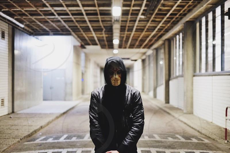 person in mask in black coat\ photo