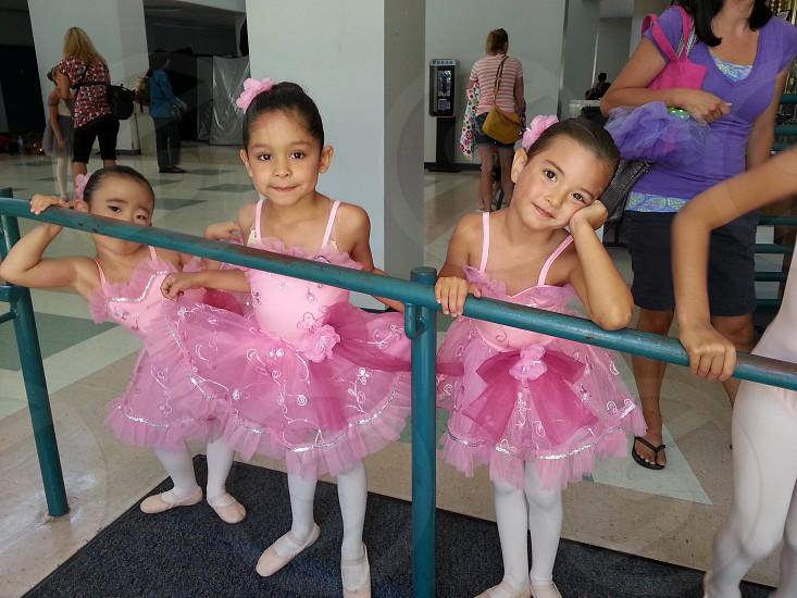 three girls wearing pink ballerina dresses standing near blue metal hand rail photo