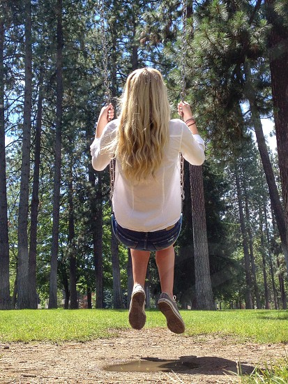 woman in white long sleeve blouse and blue shorts on a swing photo
