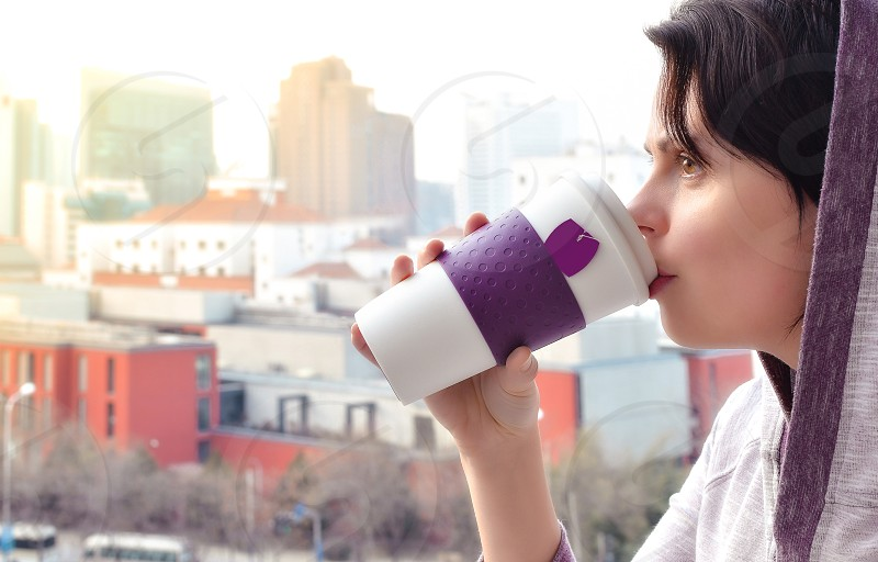 Young woman enjoying drinking tea from a travel cup during standing at the terrace with skyline view. photo