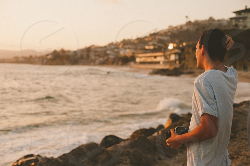 man in white tshirt holding camera with black hair overlooking ocean at sunset photo