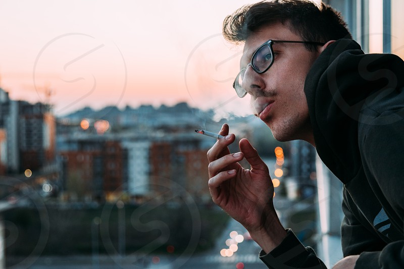 Young man smoking a cigarette on the balcony in sunset photo