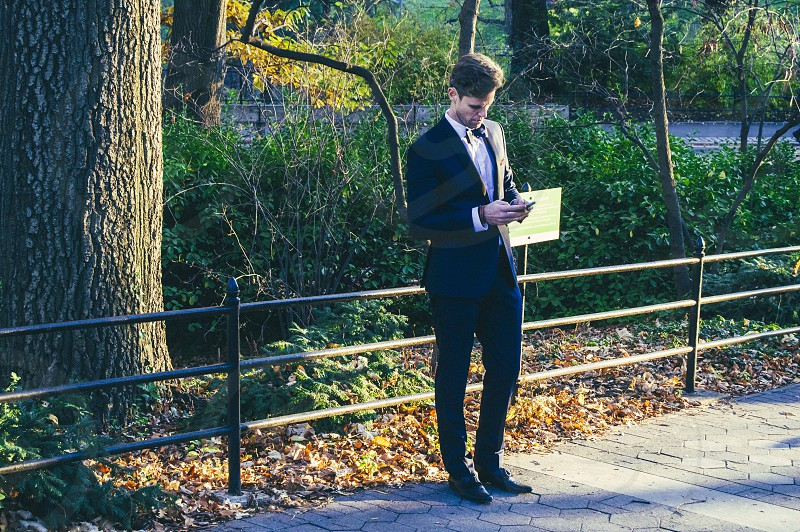 man wearing black blazer white inner shirt black dress pants holding smartphone on pathway beside rail bar and tree near road during daytime photo