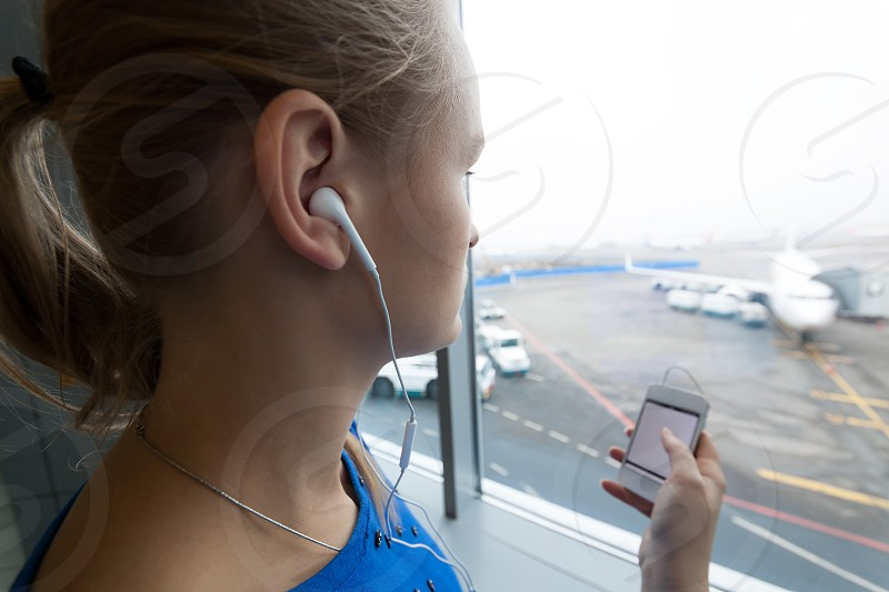 Woman listening to music using smart phone while looking out the window at airport photo